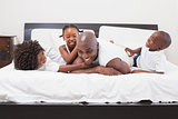 Happy family laughing together in bed