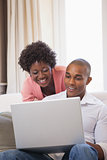 Happy couple relaxing on the couch with laptop