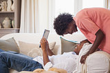 Happy couple relaxing on the couch with tablet pc