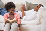 Happy couple relaxing together reading book and using smartphone