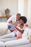 Happy couple relaxing together on the couch using tablet