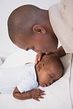 Baby boy sleeping peacefully on couch with father kissing head