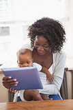 Happy mother holding baby son while using tablet pc
