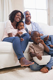 Happy family sitting on couch together watching tv