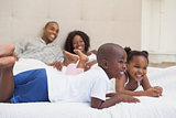 Happy family lying on bed smiling
