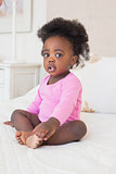 Baby girl in pink babygro sitting on bed