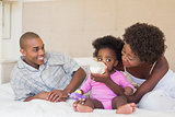 Happy parents with baby girl on their bed