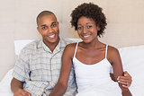 Happy couple sitting on bed smiling at camera