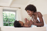 Happy mother with baby girl on changing table