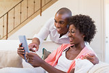 Cute couple relaxing on couch with tablet pc