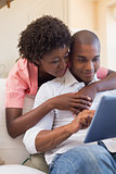 Cute couple relaxing on couch with laptop
