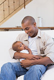 Happy father spending time with baby on the couch