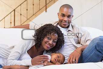 Adorable baby boy sleeping while being watched by parents