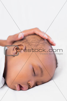 Adorable baby boy sleeping with fathers hand on head