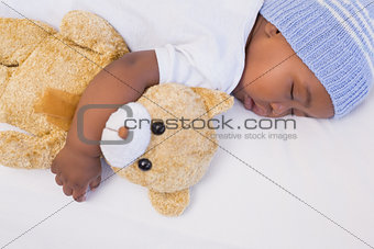 Adorable baby boy sleeping peacefully with teddy
