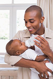 Happy father feeding his baby boy a bottle