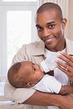 Happy father feeding his baby boy a bottle
