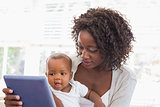 Happy mother using tablet pc with baby boy