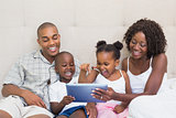 Happy family using tablet together on bed