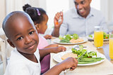 Family enjoying a healthy meal together with son smiling at camera