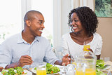 Couple enjoying a healthy meal together smiling at each other
