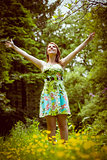 Woman with arms outstretched in field against trees