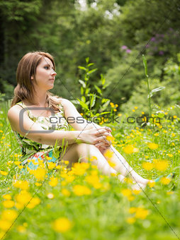 Cute woman relaxing in field