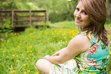 Cute young woman relaxing in field