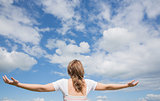 Woman with arms outstretched against blue sky and clouds