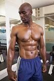 Shirtless young muscular man in gym
