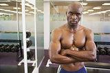 Serious shirtless muscular man in gym