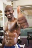 Shirtless muscular man giving thumbs up in gym