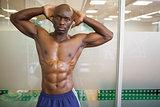 Serious shirtless muscular man posing in gym