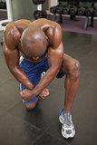 Shirtless muscular man flexing muscles in gym