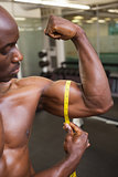 Muscular man measuring biceps in gym