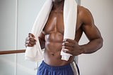 Muscular man holding towel around neck