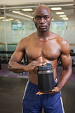 Muscular man with nutritional supplement
