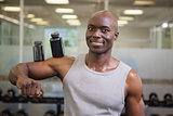 Body builder holding bottles with supplements on biceps