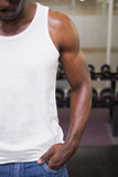 Mid section of a cropped muscular man in gym