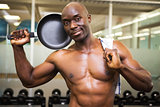 Shirtless muscular man holding frying pan in gym