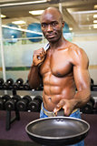 Muscular man holding frying pan in gym