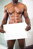 Muscular man holding blank board