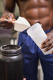 Body builder holding a scoop of protein mix
