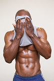 Muscular man wiping sweat after workout