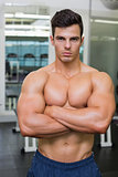 Serious young muscular man in gym