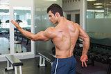 Shirtless bodybuilder posing in gym