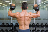 Muscular man lifting kettle bells in gym