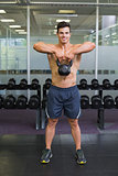 Muscular man lifting kettle bell in gym