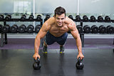 Muscular man doing push ups with kettle bells in gym