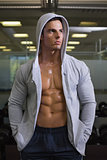 Muscular man in hood jacket at gym